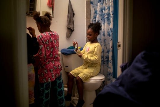 Angelina, 7, puts toothpaste on her toothbrush while her sisters brush their teeth in the bathroom on Wednesday, February 26, 2020.