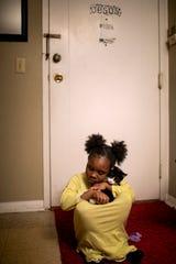 Angelina, 7, snuggles her cat, Bobo, before bedtime.