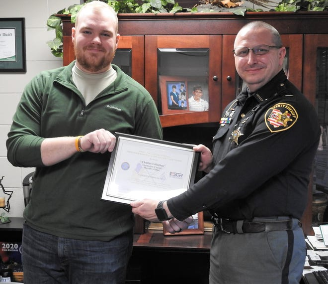 "Clay Mercer presents Charles ""Chip"" Udischas with the Patriot Award from Employer Support of the Guard and Reserve for his support and understanding regarding Mercer's military service. Udischas was in the U.S. Army Reserves himself and was in the same unit as Mercer, the 447th MP Company."