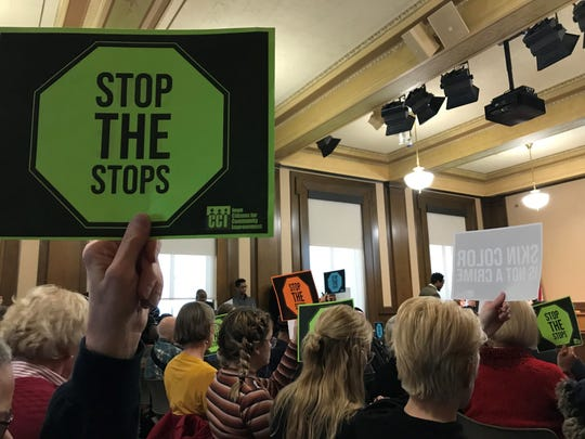 Attendees at Monday's Des Moines City Council meeting hold up signs urging the city to pan pre-textual stops by police, in which officers would stop someone for one reason before investigating something completely different.