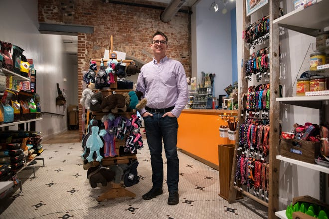 """Josh Garrett poses for a portrait in Jett and Monkey's Dog Shoppe on March 9, 2020 in Des Moines. Having owned the shop for ten years, Garrett says small business owners shouldn't be worried about increasing e-commerce in the metro — instead, """"big-box"""" retailers should be. """"Just look at Valley West Mall in the past couple years,"""" Garrett said."""