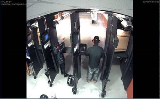 Dion Hayes, left, fires a pistol inside the Atlanta gun range, prosecutors said.