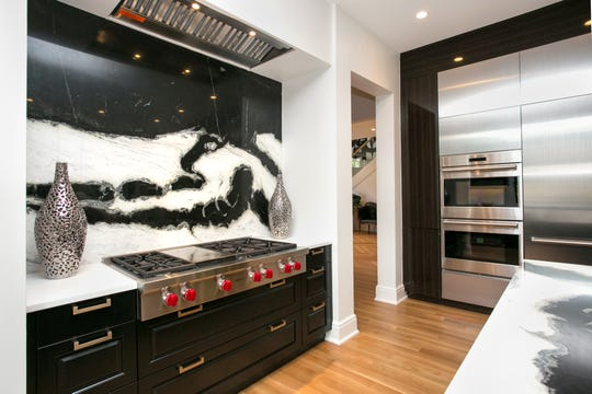 A gorgeous black and white slab tile takes the place of a traditional backsplash and pulls together the black cabinets in this Birmingham home.