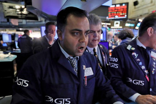 Specialist Dilip Patel, left, works at his post on the floor of the New York Stock Exchange, Monday, March 9, 2020. The Dow Jones Industrial Average sank 7.8%, its steepest drop since the financial crisis of 2008, as a free-fall in oil prices and worsening fears of fallout from the spreading coronavirus outbreak seize markets.