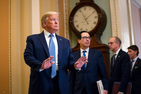 Treasury Secretary Steven Mnuchin listens and President Donald Trump arrives to speak with reporters after meeting with Republican lawmakers on Capitol Hill, Tuesday, March 10, 2020, in Washington.