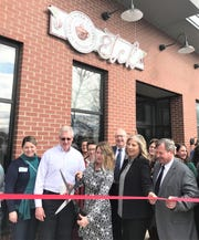 A.J. Kircher, executive director of Capabilities, cuts the ribbon Tuesday to officially open Elmira Tea & Coffee House, the latest venture operated by the agency, which provides employment opportunities for people with disabilities.