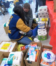 Devin Legg, back, and Yeeun Park, box up donations after the party.