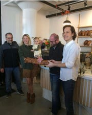 From left, Alderman Brian Johnson, Voyageurs Bakehouse co-owner Celeste Parins, Green Bay Mayor Eric Genrich and Voyageurs Bakehouse co-owner Ben Cadman held a ceremonial bread cutting during preview events on March 6 and 7.