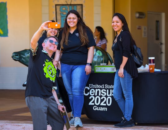 University of Guam President Thomas Krise, front, takes a selfie with Census 2020 Guam representatives during Charter Day festivities at in this March 10, file photo. All field activities for the 2020 Census of Guam have been suspended.