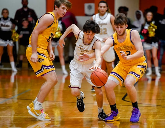 Webster County's Tyler Camplin (2) brings the ball up under pressure from Lyon County's Justin Crawford (33) as the Webster County Trojans play the Lyon County Lyons in the Second Region boys semifinals Monday evening at Hopkinsville High School, March 9, 2020.