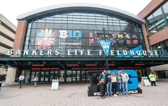 Fans pose for photos outside of Banker's Life Fieldhouse before the NCAA Big Ten tournament in Indianapolis, Tuesday, March 10, 2020.