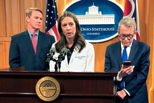"Dr. Amy Acton, Ohio Department of Health Director, center, discusses the confirmation of Ohio's first three cases of coronavirus, as Gov. Mike DeWine, right, studies an update on the cases provided to him during a news conference, Monday, March 9, 2020, in Columbus, Ohio. Lt. Gov. Jon Husted is at left. Acton said the state is ""leaning in and taking an aggressive approach"" to combating the disease. (AP Photo/Andrew Welsh-Huggins)"