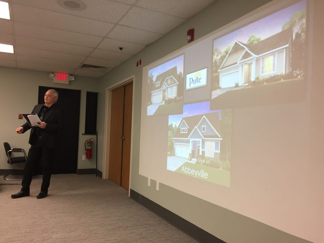Mike Noles shows examples of Pulte Homes single-family homes during a public hearing on the proposed The Bluffs at Spring Hill 70-home development in Brighton, Monday, March 9, 2020.