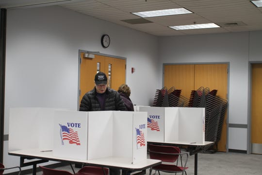 Brighton residents Greg Parish (front) and Janice Parish each cast their vote on the Democratic primary ballot for candidate Joe Biden on Tuesday, March 10, 2020 in Precinct 1 at the Brighton District Library.