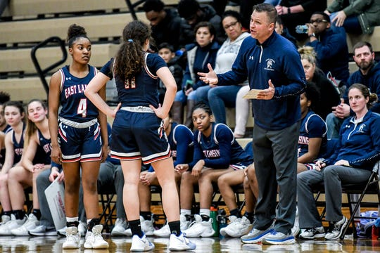 East Lansing's head coach Rob Smith, right, talks with Soraya Timms, center, and Sanaya Gregory during the first quarter on Tuesday, March 10, 2020, at Holt High School.