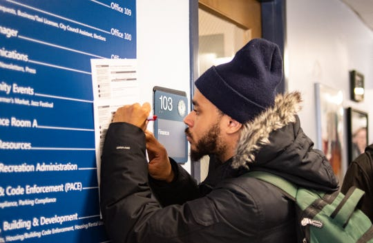 MSU student Jason Dixon of Southfield registers to vote Tuesday, March 10, 2020, at the East Lansing City Clerk's office.  He was one of over a hundred in line registering to vote.