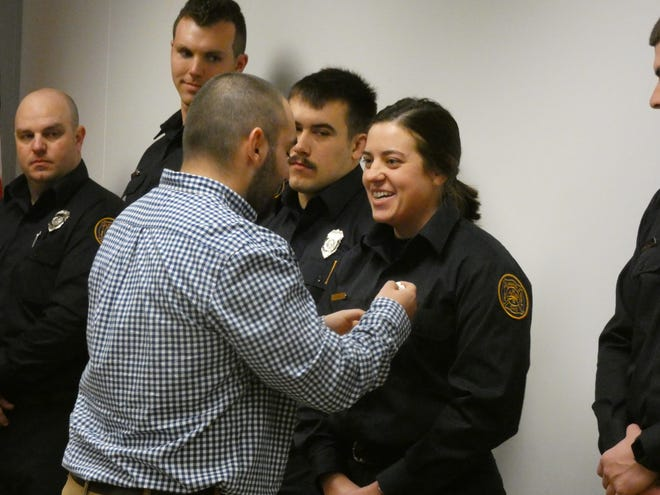Hannah Taha has her badge pinned to her shirt at a swearing-in ceremony at Marion City Hall Tuesday, where nine firefighters were sworn in to the Marion City Fire Department.