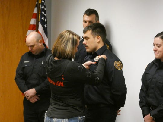 Devin Hessler, of the Waldo area, has his badge pinned to his shirt during a swearing-in ceremony Tuesday at Marion City Hall, where nine firefighters were sworn in to the Marion City Fire Department.