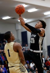 Houston's T.J. Madlock (20) goes up at the net over Arlington's Chris McKnight (1) on Monday, March 9, 2020, during the Division I Class AAA substate game at Arlington High School.