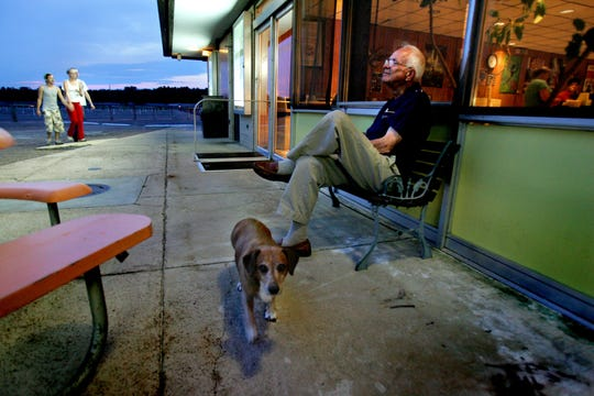 In this 2009 photo, James Lloyd sits outside the concession stand at the Malco Summer Quartet Drive-In. Mr. Lloyd, who died Monday, had worked for Malco since 1966, and lived in an apartment above the concession stand. (Also pictured: Mr. Lloyd's late dog, Duke.)