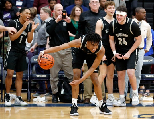Houston's Alden Applewhite (2) dribbles the ball in front of his bench as the game clock runs out Monday, March 9, 2020, during the Division I Class AAA substate game against Arlington at Arlington High School.