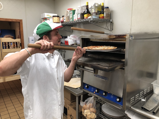 Giuseppe's Pizzeria Owner, Andrew Keark, prepares a pizza for a customer. Keark has worked in the service industry for over a decade.