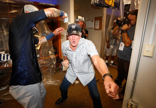 Sportscaster Bob Uecker celebrates in the clubhouse after the Milwaukee Brewers clinched a playoff berth defeating the Cincinnati Reds at Great American Ball Park on Sept. 25 in Cincinnati.