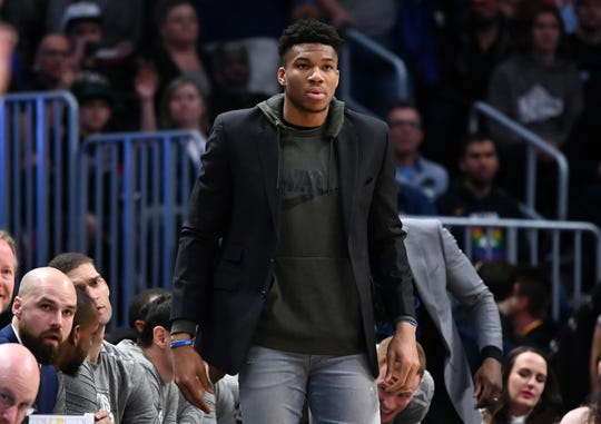 Giannis Antetokounmpo intensely watches the Bucks take on the Nuggets from the sidline.