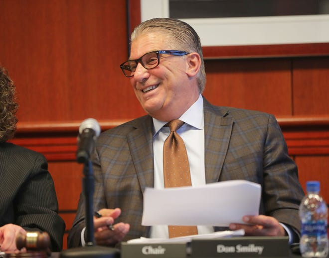 Don Smiley, chairman of the stadium district board, smiles after signing the resolution.