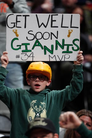 A young Bucks fan in Denver holds up a sign wishing Giannis Antetokounmpo well.