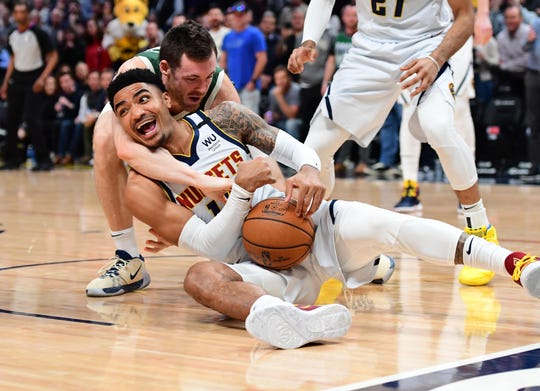 Bucks guard Pat Connaughton attempts to force a jump ball with Nuggets guard Gary Harris in the first quarter.