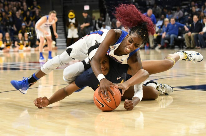 DePaul forward Chante Stonewall lands on Marquette forward Camryn Taylor as they battle for a loose ball during the Big East title game.
