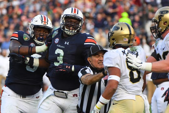Auburn defensive end Marlon Davidson (3) and Purdue Boilermakers running back Markell Jones (8) have to be separated during the Music City Bowl at Nissan Stadium on Dec. 28, 2018.