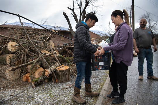 Oscar Cruz takes food supplies from volunteer Jeannette Castro outside his home along Quail Dr.  Tuesday, March 10, 2020 in Nashville, Tenn. The Cruz family is trying to rebuild their home after a tornado ripped through their neighborhood last week.