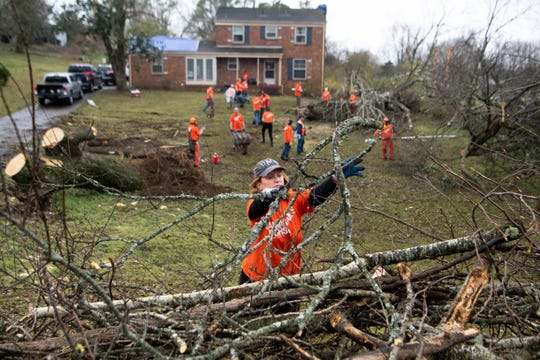 Samaritan's Purse Humanitarian aid organization volunteer Gayla Borders  throws branches in the pile of debris from a tornado in the Donelson neighborhood Tuesday, March 10, 2020, in Nashville, Tenn.