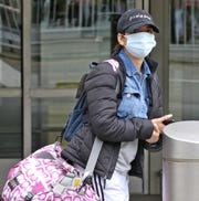 Stephanie Spencer 25 of Newark waits for a ride after arriving at Newark Airport. She wore a mask on the plane to protect herself from germs and the Corona Virus. She says that she is naturally conscious of germs due to living with younger siblings. Several passengers this afternoon arriving in Terminal B at Newark Airport were trying to protect themselves from the spread of the Corona Virus.