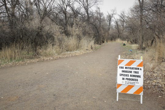 Signs placed along some trails in Farmington's Animas Park warn visitors about work being done to remove non-native species and reduce the risk of a wildfire.