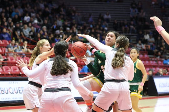 Mayfield's Kayla Avalos tries to push through three La Cueva defenders during Tuesday's NMAA 5A girls basketball state quarterfinals game at Dreamstyle Arena in Albuquerque.