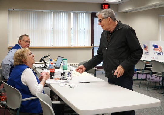 Westland voter Charles Southard checks in with election official Nancy MacDonald-Hale on March 10, 2020 to cast his ballot at Precinct 8 in the Michigan primary. By 11 am there were 53 voters at that precinct.