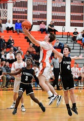 Northville's Grant Mathiesen goes up for a layup in front of a pair of Plymouth defenders.