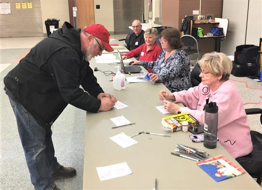 Canton Township voter Richard Sawinski fills out the necessary paperwork at Plymouth High School. Looking on are election officials (from bottom of screen) Rita Morris, Gillian Collingwood, Pat Oszust and George Dunbar.