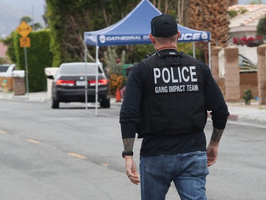 An officer with the gang impact team heads toward the Honda containing a the victim of a shooting on McCallum Way in Cathedral City, March 10, 2020.