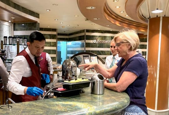 A barista serves coffee wearing surgical-style gloves at the coffee bar on Deck 5 of the Star Princess on Sunday, March 8, 2020.