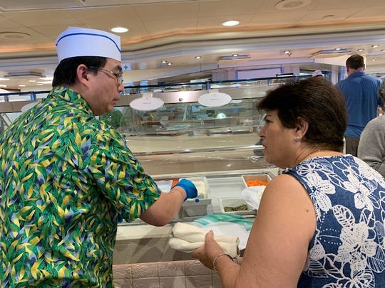 A server wearing surgical-style gloves places food on a plate for a passenger in the buffet on Deck 14 of the Star Princess on Sunday, March 8, 2020. The woman is inquiring about the change in serving procedure.
