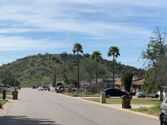 A street view of the county island neighborhood in Mesa. Mining is set to begin on the twin knolls, the hills in the background.