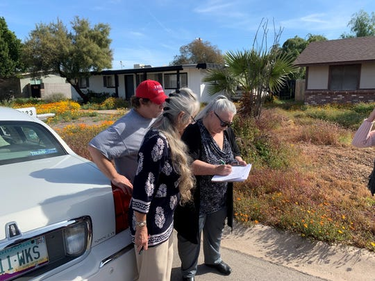 Terry Anderson signs the petition opposing mining at the twin knolls in her neighborhood as her son Roy Davis and sister Charlene Anderson look on.
