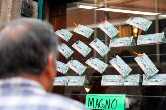 Un hombre observa billetes de lotería en una tienda expendedora en Ciudad de México. Este martes comenzó la venta de seis millones de boletos para la rifa del avión presidencial el próximo 15 de septiembre.