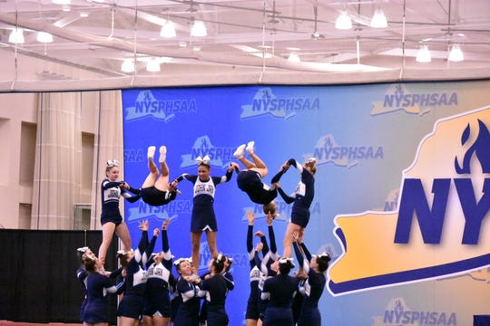 The John Jay cheerleading team performs its pyramid stunts during a routine that earned it third place in the state tournament on March 7.