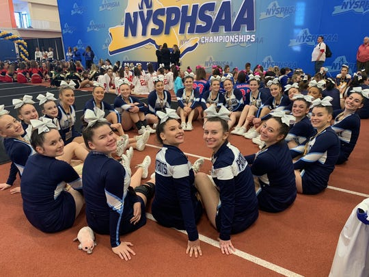 The John Jay cheerleading team sits together awaiting results of the state championships on Saturday.