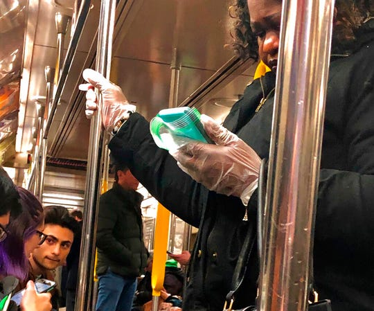 A woman uses protective gloves as she looks at her phone wrapped in a plastic bag while riding a New York City subway train, Monday, March 9, 2020. (AP Photo/Richard Drew)